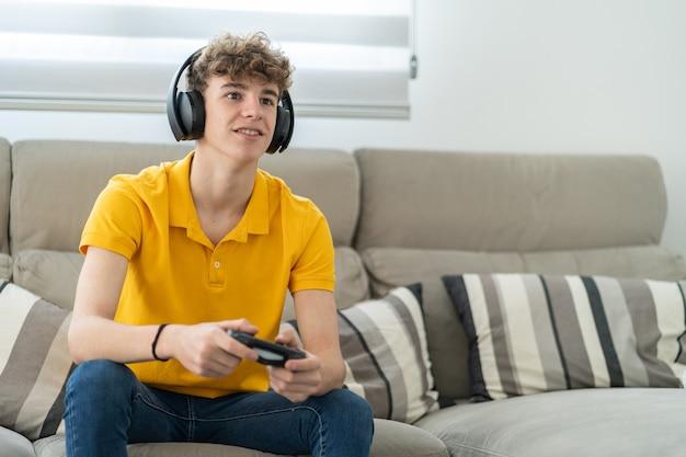 Красивый молодой парень играет на игровой консоли с наушниками и контроллером в своей гостиной
