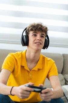 彼のリビングルームでヘッドフォンとコントローラーを備えたゲーム機をプレイするハンサムな若い男