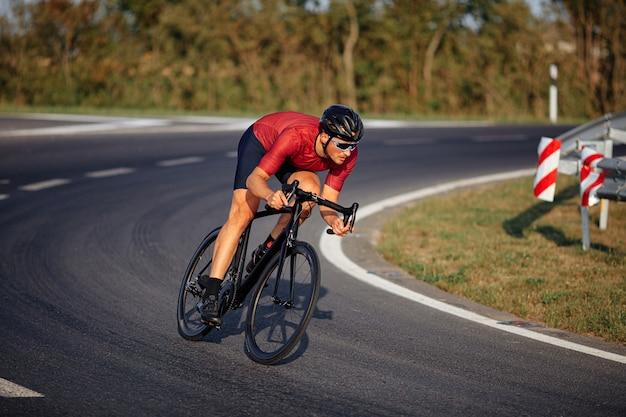 보호 헬멧과 미러 안경에 잘 생긴 젊은 남자가 타고 자전거