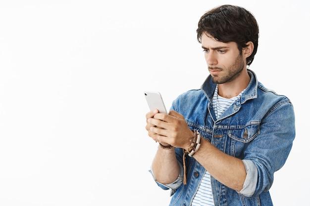 英俊的年轻人Stuggle捉住wifi作为尝试的联络朋友站立困惑和严肃在牛仔布夹克拿着智能手机看在白色墙壁上的小配件屏幕