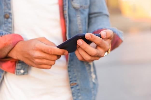 携帯電話を使用して屋外を歩くハンサムな若い男