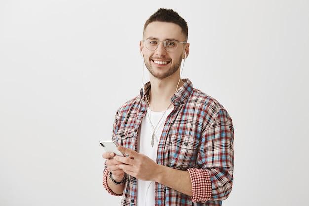 彼の携帯電話とイヤホンでポーズをとって眼鏡をかけたハンサムな若い男