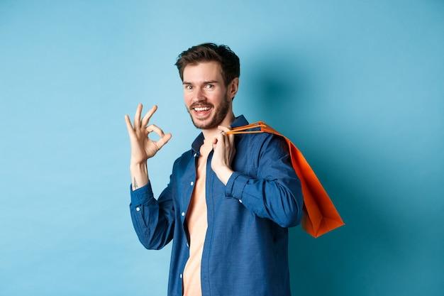쇼핑 가방 괜찮 기호를 표시 하 고 웃 고, 좋은 거래를 찬양, 파란색 배경에 서 잘 생긴 젊은 남자.