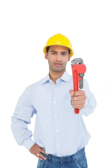 Handsome young handyman holding out a pipe wrench