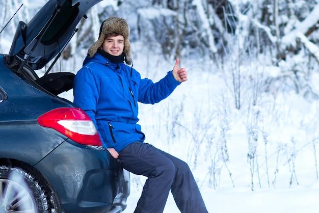 暖かい冬の服を着たハンサムな若い幸せな男は、寒い雪の日に車のトランクに座っています