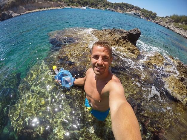 Красивый молодой счастливый турист, наслаждающийся летом и делающий селфи с мобильным телефоном, стоя на камне в море и держа маску для подводного плавания.