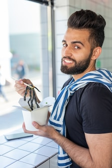 Красивый молодой хипстерский парень ест китайскую лапшу деревянными палочками, сидя в кафе и