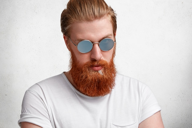 Handsome young hipster guy, has stylish hairdo, red beard and mustache, wears trendy sunglasses, dressed in white t shirt, isolated over white concrete
