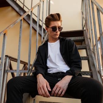 세련된 선글라스에 최신 유행의 옷에 헤어 스타일을 가진 잘 생긴 젊은 힙 스터 남자