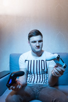 Tv 앞 소파에 앉아 있는 잘 생긴 젊은 홀링 두 개의 콘솔, 집에 있는 세트에서 푸른 빛의 정면 전망