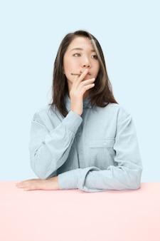 스튜디오에서 테이블에 앉아있는 동안 시가 흡연 잘 생긴 젊은 한국 여성. 무료 사진
