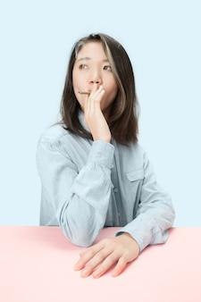 スタジオでテーブルに座っている間葉巻を吸っているハンサムな若い韓国人女性。