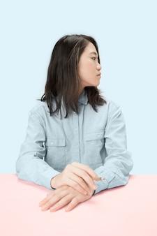 Красивые молодые корейские женщины курят сигару, сидя за столом в студии.
