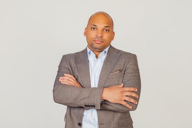 ハンサムな若い男性のアフリカ系アメリカ人のビジネスマンは、彼の胸に腕を組んで、軽薄な表情でカメラを見ています。灰色の背景の写真のポーズ。