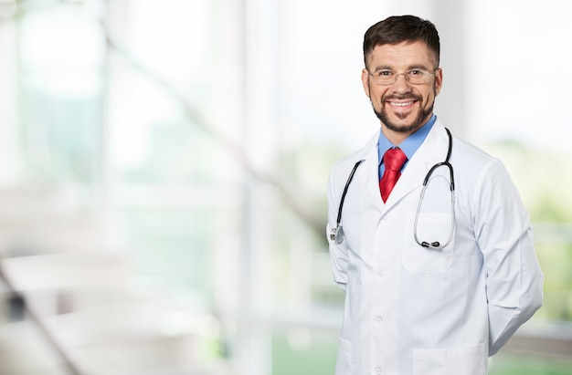 Handsome young male doctor with blurred hospital interior on background