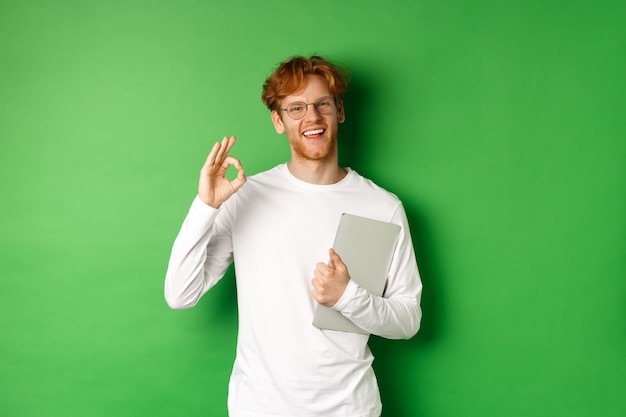 Handsome young male employee in glasses showing ok sign, holding laptop, standing over green background.