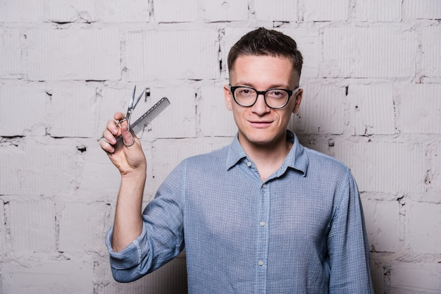 Handsome young male hairdresser in glasses, posing with scissors and comb, on gray brick wall background
