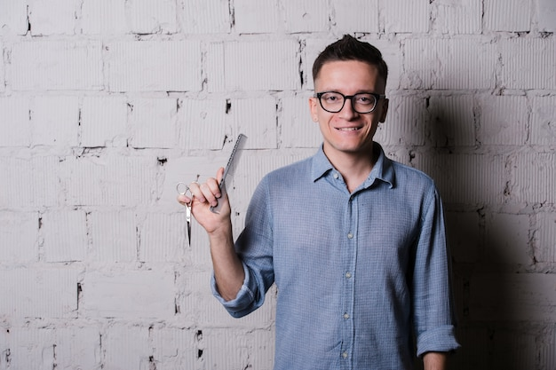 Handsome young male hairdresser in glasses smiling, posing with scissors and comb, on gray brick wall background