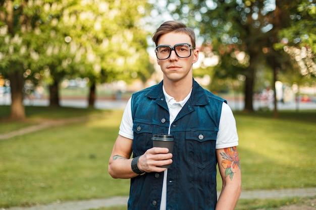 Красивый молодой мужчина-хипстер с очками и кофе гуляет в солнечный день в парке