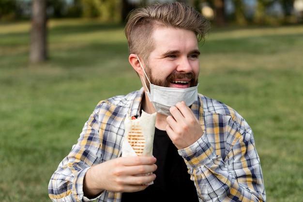 Красивый молодой мужчина, держащий кебаб