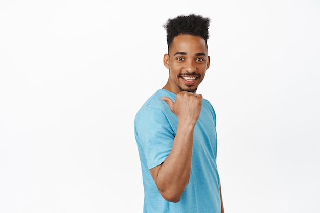 Bel giovane modello maschio modello, ragazzo afroamericano in t-shirt che punta il dito a sinistra, dietro la spalla, sorride e sembra felice, invita all'evento su bianco