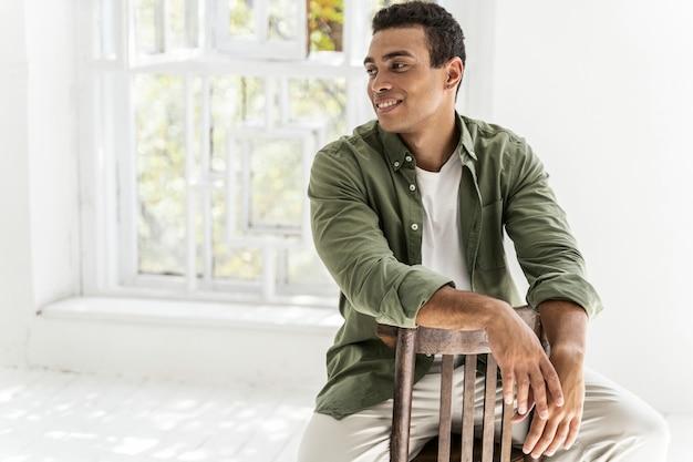 椅子に座って笑っているハンサムな若い男性