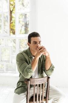 その背中に手を置いて椅子に座っているハンサムな若い男性