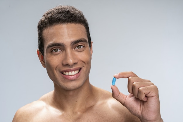 Handsome young male smiling holding a blue pill in his hand