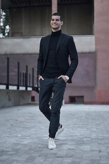 Giovane maschio bello che cammina sulla via