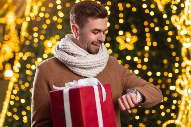 Handsome young male in warm coat and scarf holding big red gift box and checking time on wristwatch, while waiting for girlfriend near glowing christmas tree