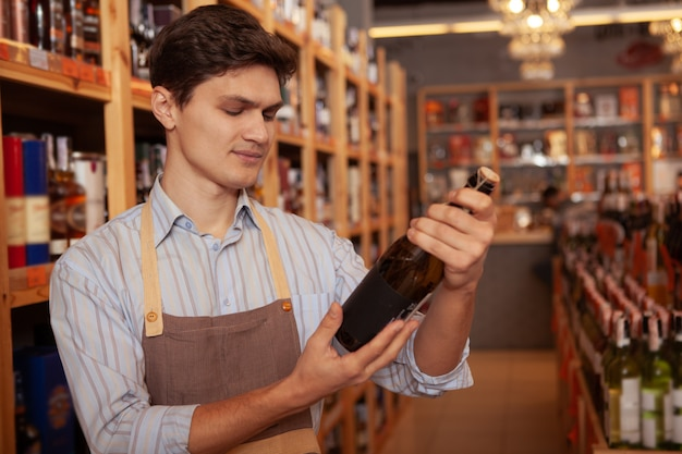 Handsome young male winemaker wearing apron, holding bottle of wine, copy space