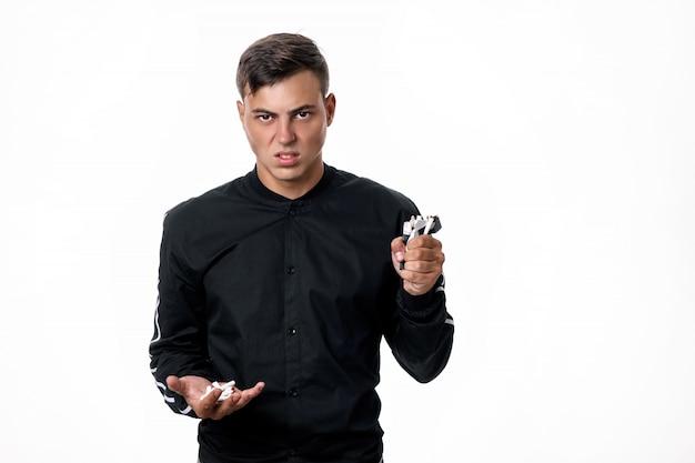 Красивый молодой человек против курения. парень позирует со сломанными сигаретами в руках на изолированном фоне