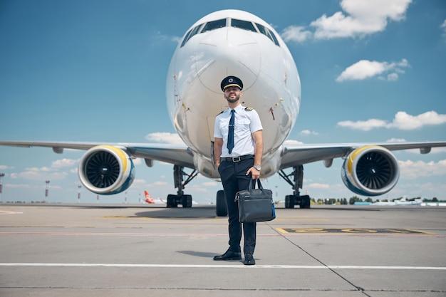 캡틴 모자 여행 가방을 들고 배경에 비행기와 공항에 서있는 동안 웃 고 잘 생긴 젊은 남자 항공사 노동자