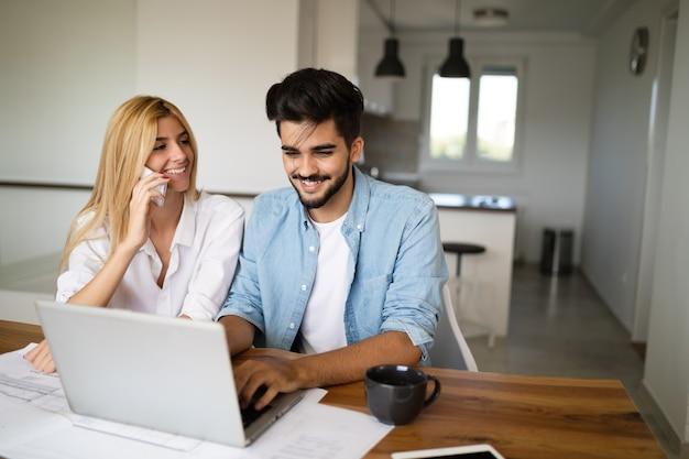 Красивый молодой человек и привлекательная женщина работают вместе на ноутбуке