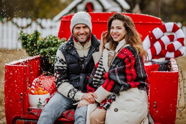 赤いクリスマスの車でポーズをとって冬の服を着たハンサムな若い男とかなり巻き毛の髪の女性