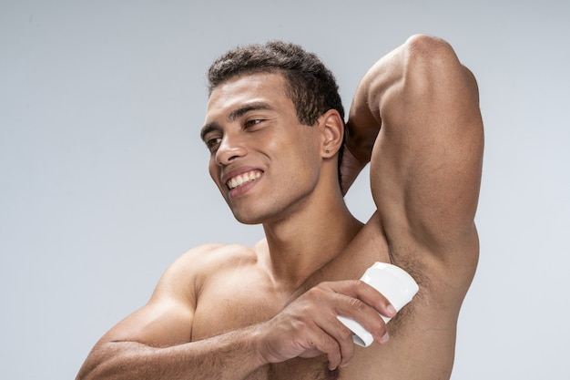Handsome young man applying his deodorant and smiling