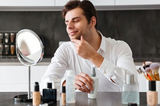 Handsome young man applying makeup and beauty products