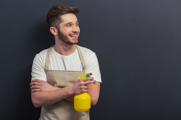 Handsome young man in apron is holding a sprayer.