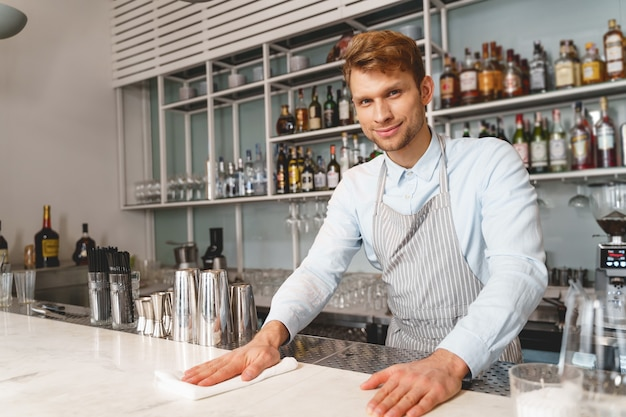 Handsome young man in apron looking and smiling while working in cafe