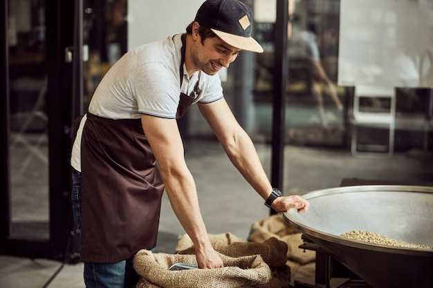 Handsome young man in apron placing hand on hopper and smiling while scooping coffee beans from burlap sack