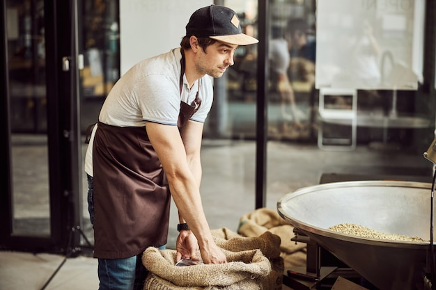 Handsome young man in apron scooping coffee beans from burlap sack