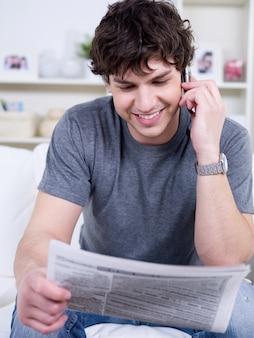 Красивый молодой человек дома разговаривает по телефону и читает газету