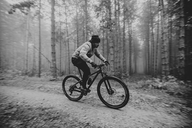 Красивый молодой человек на велосипеде через осенний лес