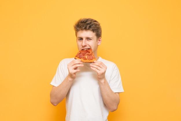 Красивый молодой человек откусывает кусок аппетитной пиццы и смотрит в камеру на желтом