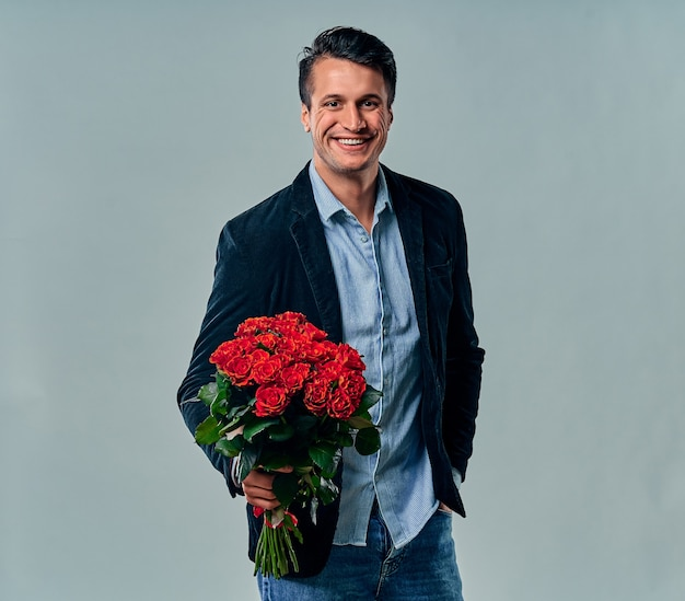 Handsome young man in blue shirt and jacket is standing with red roses on grey.
