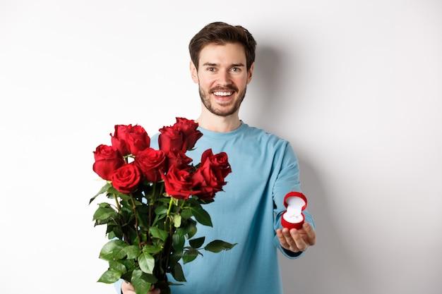 Красивый парень молодой человек делает предложение на день влюбленных валентина, держа букет красных роз и обручальное кольцо, концепцию свадьбы и отношений.