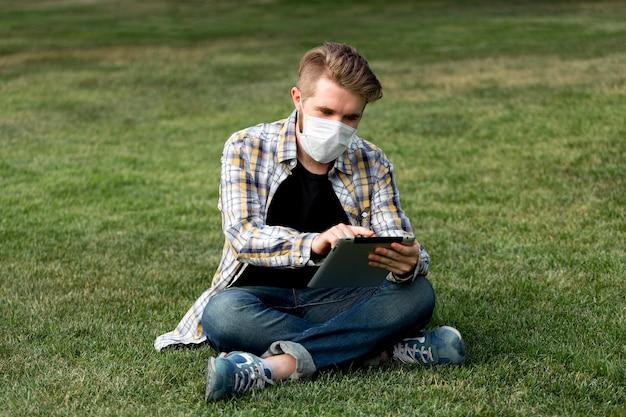 Красивый молодой человек просматривает планшет на открытом воздухе