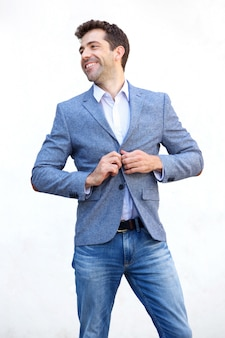 彼のジャケットを押して、白い背景で遠くを見つめるハンサムな若い男