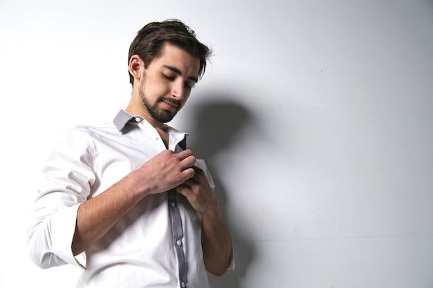 白い背景に彼の白いシャツをボタンで留めるハンサムな若い男