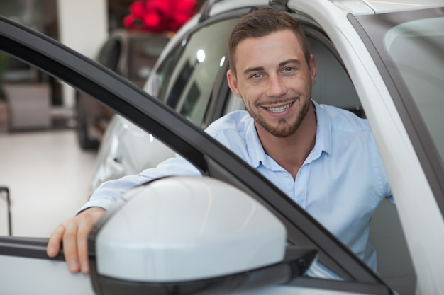 Handsome young man buying a new car at dealership salon